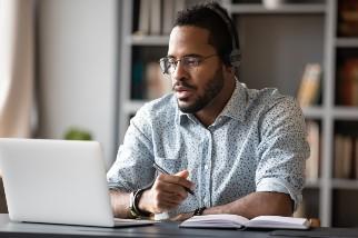 Man wearing headphones watching online training