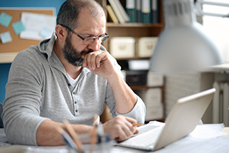 Mature adult man working in home office
