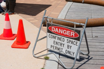 Confined space warning sign on sidewalk
