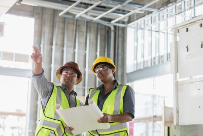 Man and woman on construction site discussing building plans
