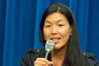 Headshot of Ai-jen Poo holding a microphone