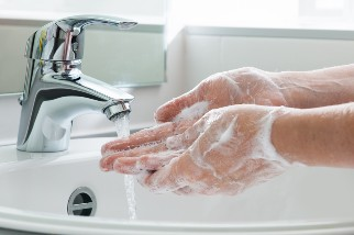 Person washing their hands in the sink