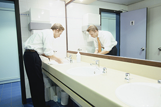 Businessman-washing-hands-in-workplace-bathroom