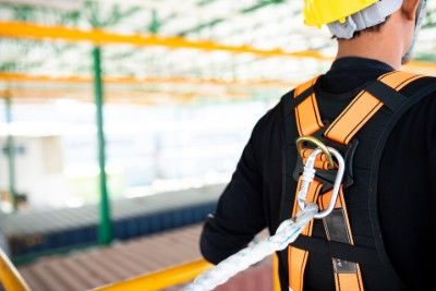 Worker wearing hard hat and harness