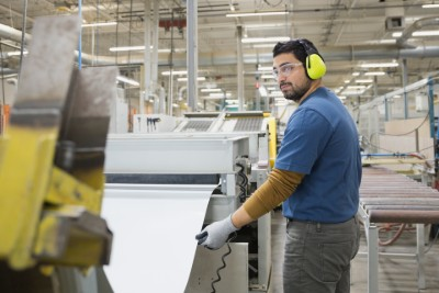 Factory worker wearing eye and ear protection