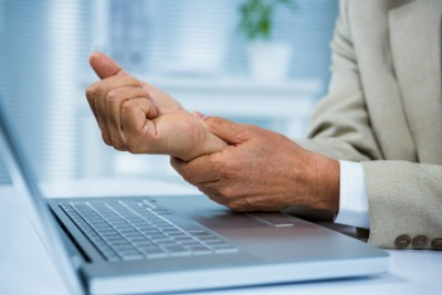 Person at computer holding wrist