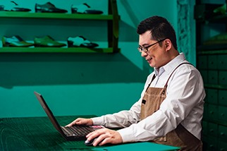Man with glasses and an apron sitting at a counter and working on a laptop in front of a teal background