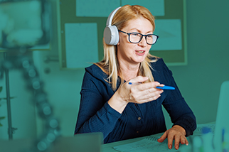 Smiling safety professional woman wearing white headphones and glasses and participating in a video call