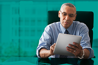 Safety professional man in blue shirt reading an OHSMS standard at his desk in front of a teal background