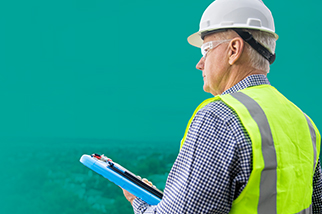 Safety professional man wearing a hard hat and high vis vest holding a tablet in front of a teal background