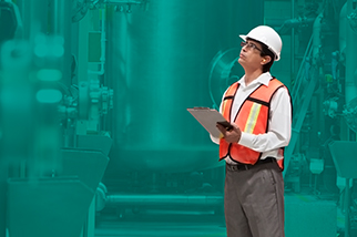Safety professional man in safety vest and a hard hat holding a clipboard in front of a teal background