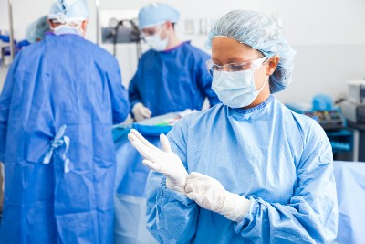Female surgeon putting on surgical gloves before operation