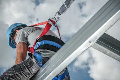 Construction worker harnessed on a steel frame building