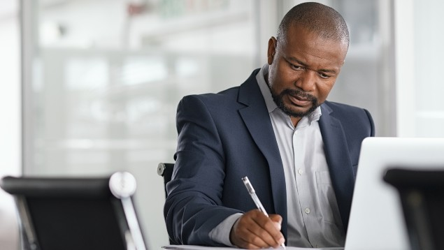 Black businessman writing on a notepad