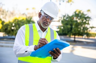 Construction manager writing on a clipboard