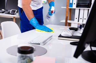 Worker cleaning and disinfecting a desk