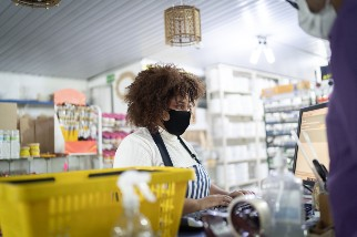 Young retail worker wearing a mask