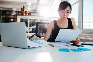 Businesswoman reading papers at her desk