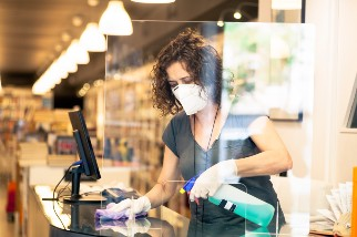 Retail worker in mask disinfecting counter