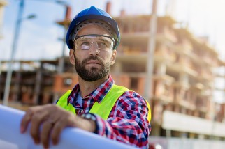 Man on a construction site looking at a blueprint