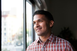 Man smiling while looking out a window