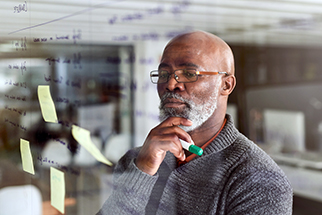 Mature Black businessman brainstorming with notes on a glass wall