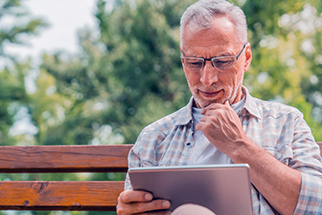Mature man reading news on digital tablet on bench