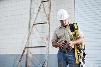 Construction worker holding a harness and gloves