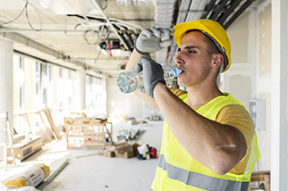 Construction-worker-drinking-water-on-hot-building-site
