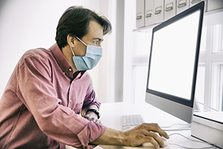Businessman-viewing-large-computer-monitor-wearing-a-face-covering