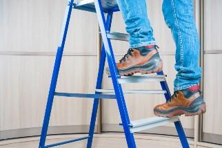 Worker walking up a ladder