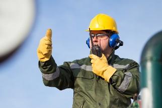 Oil rig worker wearing headphones
