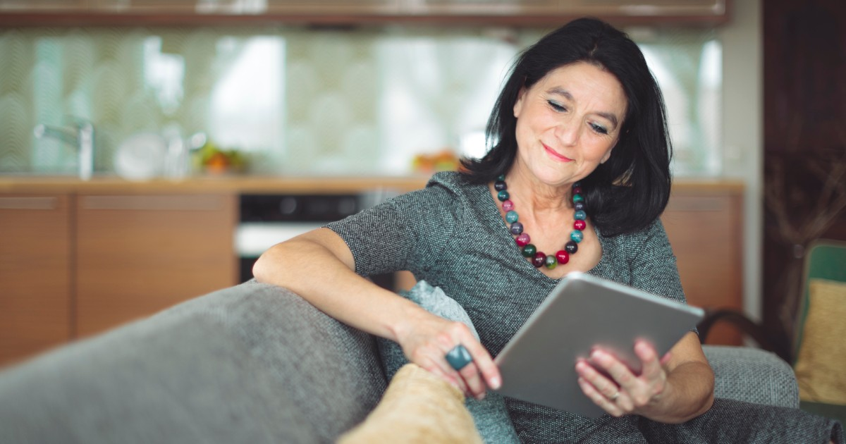 Middle aged safety professional woman reading an article about COVID-19 on her tablet at home