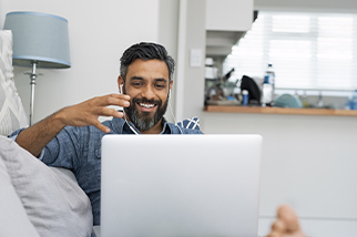 Happy man with earbuds looking at his computer on a couch
