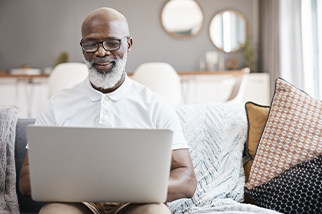 A mature man using a laptop at home